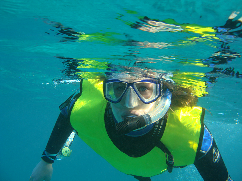 Adelphi student snorkels underwater while looking at the camera
