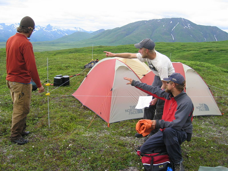 Adelphi students squatting near a tent in Alaska
